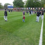 St. Paul Saints players showing the young people from Owatonna the proper pre-game stretching drills